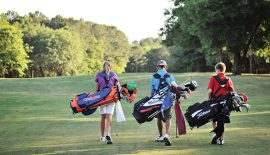 One girl and two boys walking the course with their bags.
