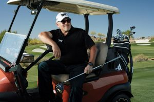 Founder Bob Parsons driving golf cart on a golf course holding a PXG iron.